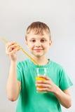 O menino engraçado pequeno está indo beber o suco de laranja fresco através de uma palha imagens de stock royalty free