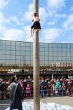 O menino escala na coluna atrás do presente durante o entretenimento de Shrovetide Imagens de Stock Royalty Free