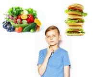 O menino escolhe entre o alimento e o fast food saudáveis fotografia de stock royalty free
