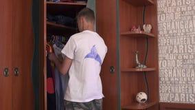 O menino escolhe a roupa no armário video estoque
