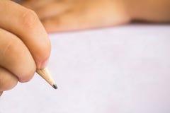 O menino escreve no Livro Branco com lápis imagens de stock