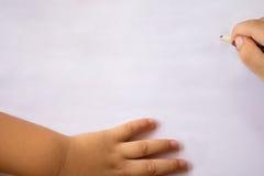 O menino escreve no Livro Branco com lápis imagens de stock royalty free