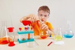 O menino esperto novo em óculos de proteção de segurança estuda a prática química no laboratório Foto de Stock Royalty Free
