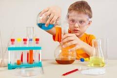 O menino esperto pequeno em óculos de proteção de segurança estuda a prática química no laboratório Fotografia de Stock Royalty Free