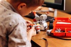 O menino esperto vestido na camisa cinzenta faz um robô do construtor robótico na mesa na escola da robótica imagens de stock royalty free