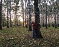 O menino está abraçando uma árvore fotografia de stock royalty free