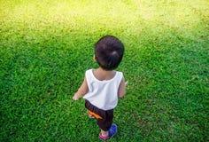 O menino está andando na grama verde em um jardim Imagem de Stock