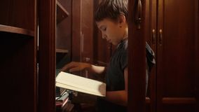 O menino está atravessando os livros na prateleira e na picareta uma filme