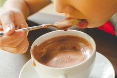 O menino está comendo o chocolate quente Imagens de Stock Royalty Free