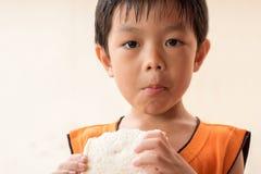 O menino está comendo o pão de forma fotos de stock royalty free