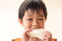 O menino está comendo o pão de forma fotografia de stock