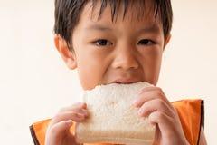 O menino está comendo o pão de forma fotos de stock