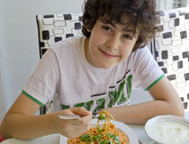 O menino está comendo os espaguetes imagens de stock royalty free