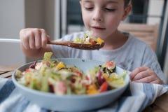 O menino está comendo a salada saudável de uma grande bacia imagens de stock royalty free