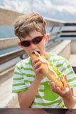 O menino está comendo um sanduíche Imagem de Stock