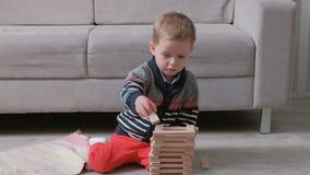 O menino está construindo uma torre dos blocos de madeira que sentam-se no assoalho pelo sofá vídeos de arquivo