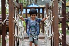 O menino está cruzando a ponte de corda na terra do jogo Fotos de Stock Royalty Free