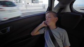 O menino está dormindo no carro na maneira filme