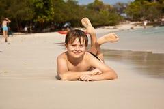 O menino está encontrando-se na praia bonita Foto de Stock