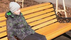 O menino está esperando seus pais que sentam-se no parque em um banco video estoque