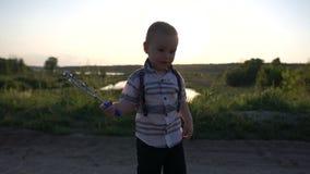 O menino está estando e está movendo ativamente a varinha da bolha no sol, movimento lento filme