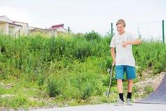 O menino está estando no skatepark e está mostrando os gostos foto de stock