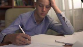 O menino está estudando em casa vídeos de arquivo