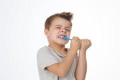 O menino está ferindo ao limpar os dentes Fotografia de Stock