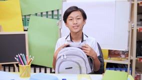 O menino está guardando um alforje em seu regaço, sentando-se em uma tabela e em um sorriso vídeos de arquivo