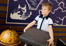 O menino está guardando um livro A sala com o globo foto de stock
