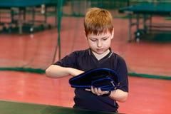 O menino está guardando uma tampa para uma raquete para o tênis de mesa imagens de stock