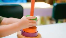 O menino está jogando com a pirâmide rainboy de madeira colorida do brinquedo imagens de stock royalty free