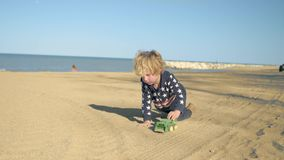 O menino está jogando com um caminhão basculante do verde do brinquedo na praia filme