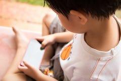 O menino está jogando o jogo no telefone celular fotos de stock royalty free