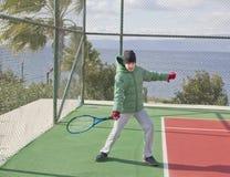 O menino está jogando o tênis Fotografia de Stock