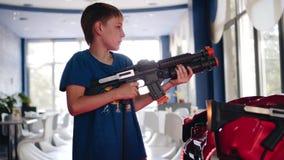 O menino está jogando um jogo do tiro do divertimento na arcada As emoções das crianças frescas video estoque