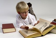 O menino está lendo livros grossos Imagens de Stock Royalty Free
