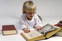 O menino está lendo livros grossos Foto de Stock Royalty Free