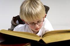 O menino está lendo livros grossos Imagem de Stock Royalty Free