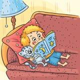 O menino está lendo um livro com seu gato Imagens de Stock Royalty Free