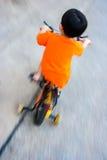 O menino está montando a bicicleta fotografia de stock
