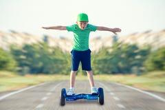 O menino está montando em uma placa do equilíbrio imagem de stock
