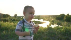 O menino está no sol e come o bolo no movimento lento no por do sol filme