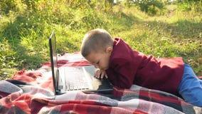 O menino está olhando o computador