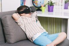 O menino está olhando o vídeo com vidros da realidade virtual, dentro Dispositivo da realidade virtual de Digitas Fotos de Stock Royalty Free