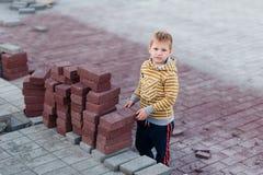 O menino está perto dos tijolos da construção colocando pavimentos Crianças e a profissão imagens de stock royalty free