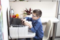 O menino está sentando-se em uma mesa na frente de um portátil Ambas as mãos no toque do teclado a placa de controle do cursor foto de stock