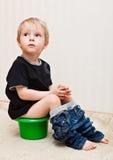 O menino está sentando-se no potenciômetro imagem de stock royalty free