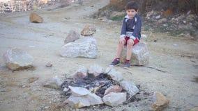 O menino está sentando-se pelo fogo extinto video estoque