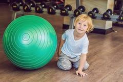 O menino está sentando-se perto do fitball no gym fotos de stock royalty free